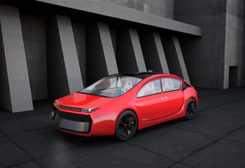 Red electric car in front of geometric object background.
