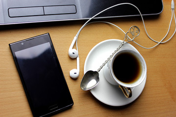 Black smartphone and coffee cup on a table isolated on white background.