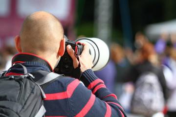 Uomo calvo fotografa con teleobiettivo