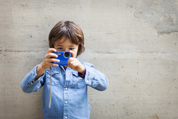 Little boy taking a picture with digital camera