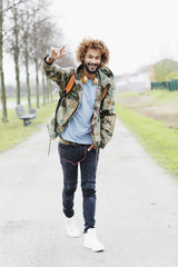 Portrait of happy man with dyed ringlets wearing camouflage jacket
