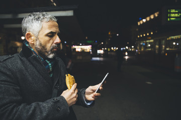 Austria, Vienna, man with Cheese Carniolan sausage looking at his smartphone by night
