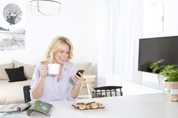 Smiling woman sitting at the table in her living room holding coffee cup while looking at smartphone