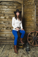 the girl cowboy sitting on wooden background wall in the hands of a gun