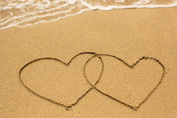 Couple of hearts drawn on the beach sand in sunny day.