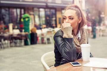 Beautiful woman drinking coffee at the cafe / Pretty young woman drinking coffee with her mobile phone
