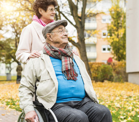 Senior woman with husband in wheelchair outdoors