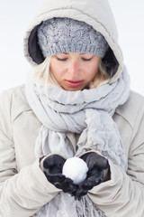 Cute casual young woman wearing glooves, woolen cap and scarf, holding icy snowball in cold winter time. Lady looking down at snowball.