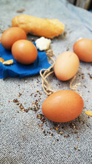 yellow eggs lie on blue napkin with slices of baguette and a rope
