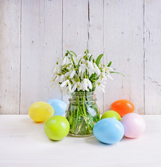 snowdrops and Easter eggs on wooden background