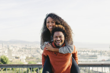 Spain, Barcelona, portrait of laughing young man giving his girlfriend a piggyback ride
