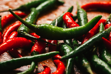 red and green chili peppers close up on wooden background