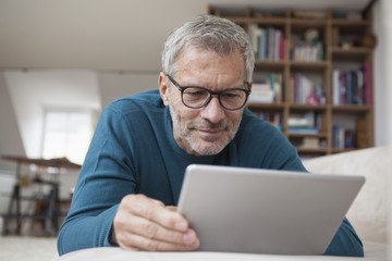 Mature man at home lying on couch using digital tablet