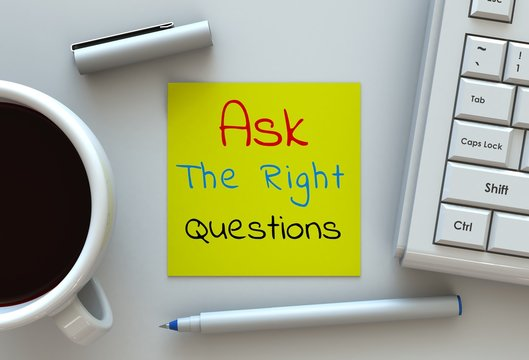 Ask The Right Questions, message on note paper, computer and coffee on table