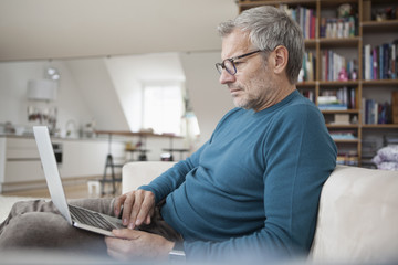 Mature man at home sitting on couch using laptop