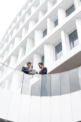 Poland, Warzawa, two businessmen with tablet computer standing in front of hotel