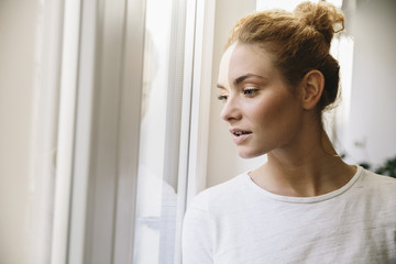 Young woman looking out of her window, being stroke by sunlight
