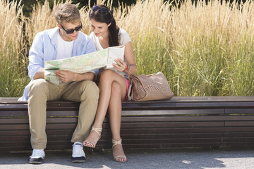 Poland, Warsaw, Young couple reading map on bench