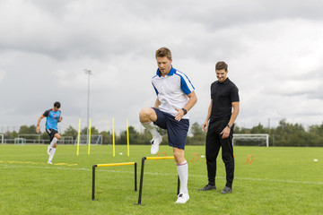 Coach exercising with soccer players on sports field