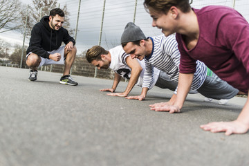 Young man motivating his friends, pushups