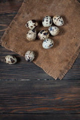 Quail eggs on a wooden table with copy space. Top view