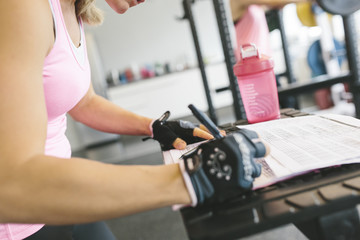 Woman planning her workout routine in gym