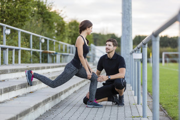 Man looking at woman exercising on sports field
