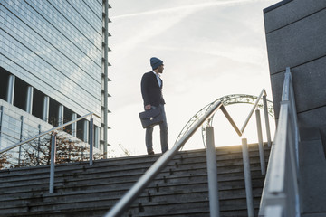 Germany, Frankfurt, Young businessman standing on stairs, looking away