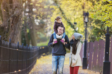 Family going for a walk in autumnal park