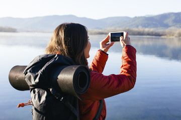 Spain, Catalunya, Girona, female hiker taking a cell phone picture at a lake