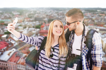Young couple of travelers taking selfie on cityscape background
