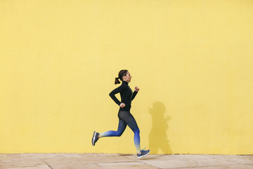 Spain, Barcelona, jogging woman in front of yellow wall