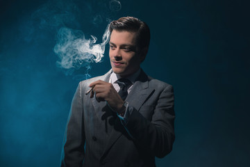 Vintage 1940s business man in suit and tie smoking cigarette aga
