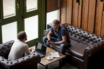 Two men with laptop sitting on couch in a lounge