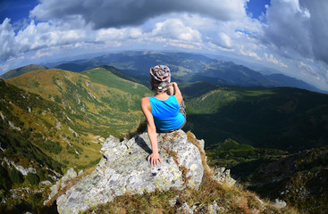 Young woman  sitting on a stone   in mountains, Carpathian ,Ukraine
