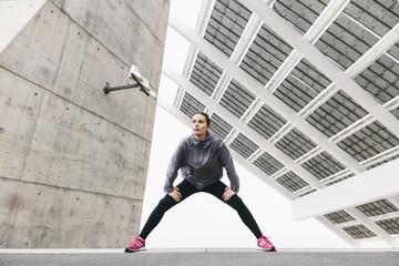 Spain, Barcelona, jogging woman under solar plant