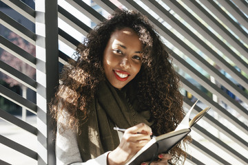 Portrait of smiling young woman with notebook outdoors