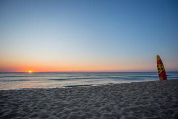 Surfbrett im Sonnenaufgang am Meer