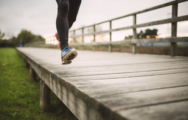 Spain, Naron, legs of a jogger running on a boardwalk