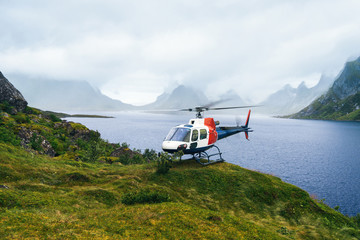 Helicopter in the great Norwagian mountains in cloudy weather. Reine, Lofotens