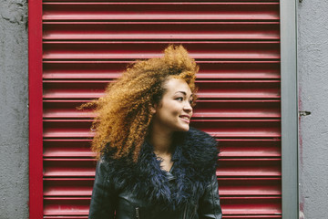 Ireland, Dublin, smiling woman with afro in front of red roller shutter