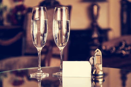 Full champagne glasses, antique keys and blank white card. Luxury hotel apartment