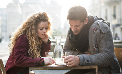 Italy, Milan, couple sitting at sidewalk cafe looking at smartphone