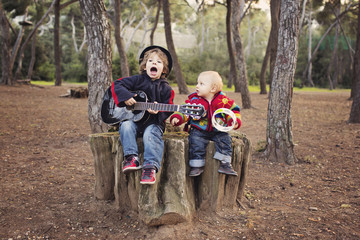 Little boy playing guitar and singing for his baby brother in a forest