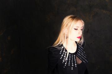 Portrait of emotional blond girl in black wear in studio