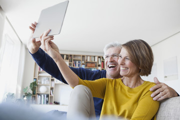 Happy couple sitting on the couch at home taking a selfie with digital tablet
