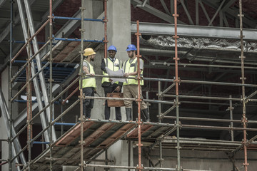 Construction workers and businessman discussing building plan on scaffolding