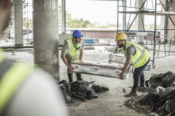 Two construction workers carrying item in construction site