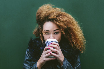 Portrait of woman drinking coffee in front of green wall