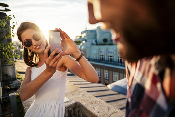 Austria, Vienna, smiling young woman taking a photo of her boyfriend on a roof terrace